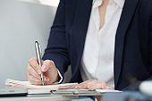 Entrepreneur taking notes in planner