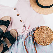 Summer holiday clothes. Female fashion outfit - skirt, top, hat, bag, sandals. Top view, flat lay
