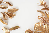 Gold tropical palm leaves Monstera on white background. Flat lay