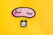 Sleep concept showing an eye mask and an alarm clock on a yellow background. copy space