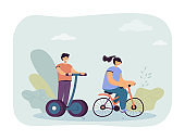 Girl riding bicycle and boy on electric personal transporter