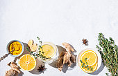 Immune boosting remedy. Flat lay  with ingredients from turmeric, thyme, lemon, star anise and glass water with lemon on white background with hard shadows.