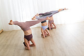 Portrait of active sporty young women practicing standing on head yoga pose in yoga studio. Healthy active lifestyle, working out indoors in gym.