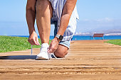 closeup of woman tying shoe laces. Female sport fitness runner getting ready for jogging outdoors in spring or summer.