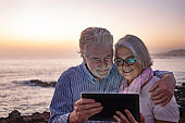Embraced attractive senior couple white-haired looking at digital tablet in the dusk sitting on the beach with horizon over water on background. Happy retirement concept together