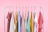Collection of pastel colored women clothes hanging on rack in dressing room isolated on pink background