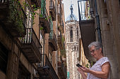 Senior woman traveling in Barcelona uses mobile phone resting. Old cathedral in the background