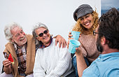 Four people having fun and laughing together sitting outdoor on the terrace with food and drink.  Beautiful people in friendship
