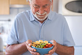 Smiling senior man ready to eat a salad of fresh and dried fruits. Breakfast or lunch time, healthy eating
