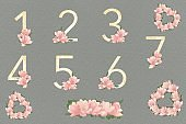 A template for seating guests with gold numbers and compositions of pink flowers on a dark green textured background