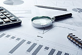 Closeup of magnifier glass, calcilator on the business profit documents.Concept of profit growth