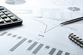Profit report, charts of costs, pen calculator on the workplace.Analyzing of business documents