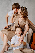 A mother and sons in beige and white clothes pose for a photo shoot