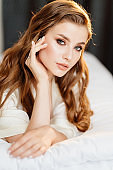 close up. portrait of beautiful woman with long hair in robe lying on bed.