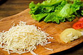 grated cheese on a wooden cutting board. lettuce and chopped tomatoes