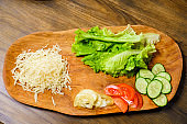grated cheese, lettuce, ringed tomato and cucumber on a wooden cutting board.