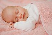 sleeping baby under the pink blanket. healthy sleep in newborns.