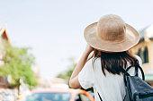 Teenager traveller asian girl wear hat rear view.