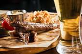 Grilled sausages with beer and vegetables with pickled cucumber, cabbage salad sauce and bread on parchment, top view.