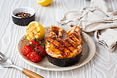 Grilled salmon steak glazed with teriyaki sauce, vegetables and lemon served on ceramic plate on rustic white wooden table from angle view, selective focus