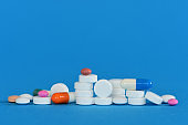 Medicine pills, tablets and capsules, on blue background.