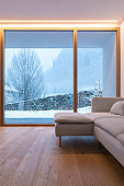 Detail of modern sofa in living room with large windows, view of nature and snow