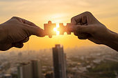 Two hands connect pieces of the puzzle against the sunset. Business concept idea