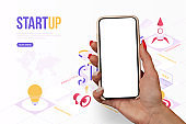 Startup concept. A girl with beautiful nails holds a smartphone mockup in her hand against the background of design work.