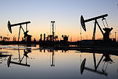 Oil field site, in the evening, oil pumps are running
