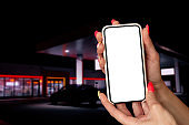 Mock up smartphone in hand closeup on the background of a gas station with car. Payment refueling online.