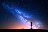 Beautiful Milky Way with standing woman. Colorful landscape with night sky with stars and silhouette of a girl on hill on the background of beautiful galaxy. Blue milky way with yellow light. Space