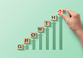 Wooden blocks arranged in a staircase with the word GROWTH and increasing arrows on green background. Business growth, career growth or growth concept.