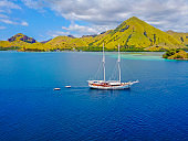 Aerial view of beautiful scenery at Flores island with tourist yatch, turqouise and dark blue sea.