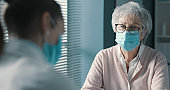 Doctor talking with a senior woman in her office