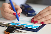 Agent filling out car insurance documents with pen