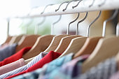 Colorful casual clothes hang on hangers closeup