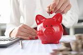 Woman throws coin into piggy bank closeup