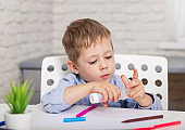 Cute little boy cutting colorful paper at home. Creative kid