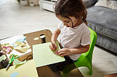 High angle view of an adorable girl drawing shapes on a green paper sitting at a table at home