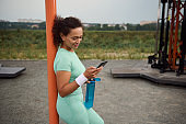 Serene sporty beautiful young African American woman holding bottle with water and checking mobile application on her mobile phone, leaning on cross bar, resting after sport activities in sports field