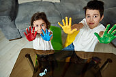 Adorable boy and girl, showing their hands painted in red, blue, yellow and green paints to the camera. Creative hobby. High angle view