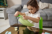 Adorable little preschool girl with braids sitting at the table and concentrated on cutting shapes from color green paper.