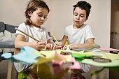 Beautiful school boy and preschool girl drawing during art creativity class at home