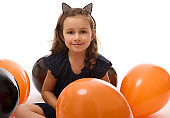 Portrait of cute 4 years old witch girl in Halloween costume with colorful black and orange balloons isolated on white background with copy space. Halloween party.