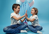 Boy and girl clapping hands while posing on blue background with balloons behind them