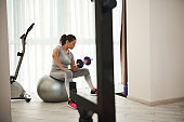 Beautiful sporty woman pumping biceps with dumbbell while sitting on fitness ball at home gym