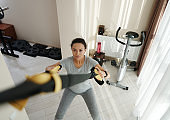 High angle view of athletic woman exercising at home with fitness straps.