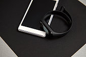 Mobile phone and digital watch or black fitness tracker on a black sheet of paper on a gray background. Black and white still life. Flat lay