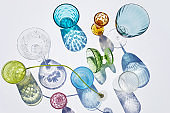 Summer still life scene. Glittering glasses of water or cocktails on white table background in sunlight. Long harsh shadows. Vacation concept