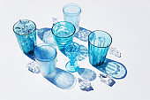 Summer still life scene. Glittering glasses of water or cocktails with ice cubes on white table background in sunlight. Long harsh shadows.